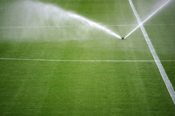 Rasensprenger Fußballfeld / Die grüne Rasenfläche eines Fußballfeldes mit einer Bewässerungsanlage.