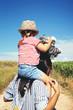 Madre lleva a hombros a su hija pequeña en un paseo por el campo