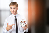 Successful businessman in formal wear pointing at clock - 220783891