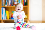 Adorable baby girl playing with educational toys in nursery. Happy healthy child having fun with colorful different toys at home. Baby development and first steps, learning to play and to grab. - 220784240