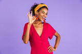 Image of cheerful happy woman 20s in hair band smiling and showing ok sign, isolated over violet background - 220787074