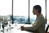 Backlit side view portrait of young successful businesswoman sitting at table in conference room and taking notes, copy space - 220790458