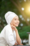 Pretty Asian woman in white towel and soft bathrobe standing outdoors in sunshine looking away with smile - 220790476