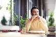 Young man enjoying taste of original Italian pizza while sitting in modern cafe - 220792001