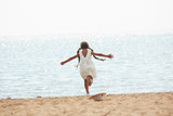 Back view portrait of carefree teenage girl running to sea happily stretching her arms, copy space - 220794049