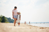 Full length portrait of loving modern mom embracing daughter while enjoying walk along beach during Summer vacation, copy space - 220794457