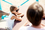 High angle portrait of smiling little girl wearing sunglasses sitting in outdoor cafe with parents enjoying Summer vacation, copy space - 220794674