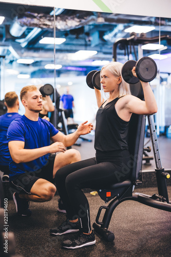 Leinwanddruck Bild Woman lifting weights, exercising with personal trainer.
