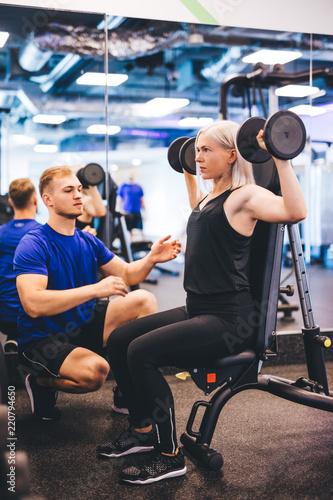 Leinwandbild Motiv Woman lifting weights, exercising with personal trainer.