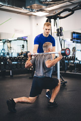 Senior man exercising with personal trainer.
