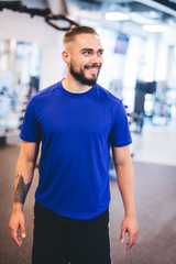 Smiling man standing in a gym.