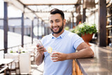 Waist up portrait of handsome Middle-Eastern man looking at camera and smiling while using smartphone leaning on bar counter in outdoor terrace - 220809051
