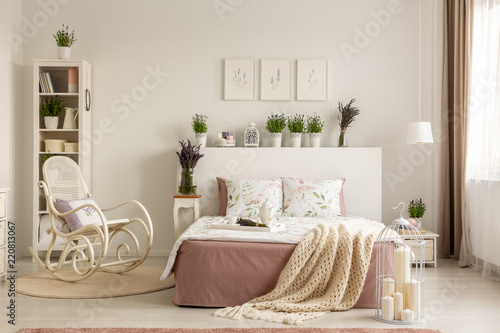 Rocking chair next to bed with blanket in provencal bedroom interior with plants and posters. Real photo - 220813067