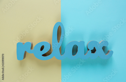 Word Relax made of wooden letters lies on the blue and yellow background. Motivation word. Flat lay, copyspace - 220818070