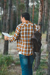 back view of tourist with map and backpack in forest