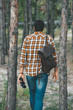 back view of tourist with backpack and binoculars walking in forest