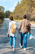 back view of tourists with backpacks holding hands while walking on road together