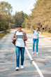 selective focus of man with map and girlfriend with binoculars behind on road