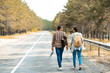 back view of tourists with backpacks walking on empty road