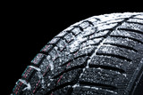 Winter car tires with snow wheel profile structure on black background - Close up - 220830281