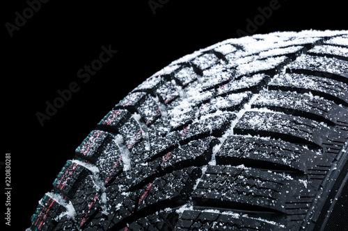 Poster Winter car tires with snow wheel profile structure on black background - Close up
