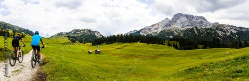 Leinwanddruck Bild Mountain cycling couple with bikes on track, Cortina d'Ampezzo, Dolomites, Italy