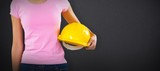 Composite image of woman holding hard hat against grey - 220836828
