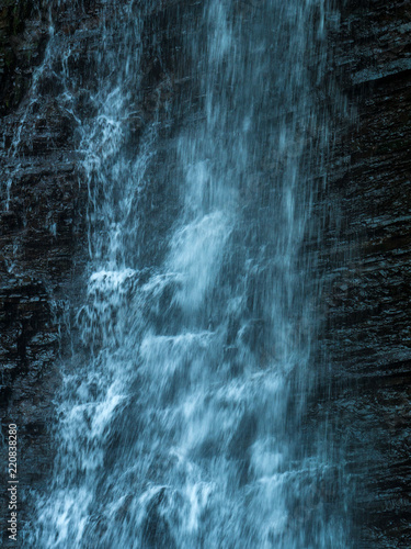 Mountain waterfall with blue, clear water. Summer background