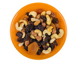 Mix of nuts and dried fruits in bowl on white - 220847603