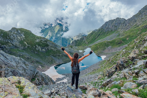 Leinwanddruck Bild Happy successful tourist with pony tale with raised arms on rock at mountains near cold mountain lake