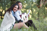 young couple sitting in the forest and playing guitar, summer nature, bright sunlight, shadows and green leaves, romantic feelings - 220852619