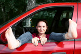 young woman driver resting in a red car, put her feet on the car window and flirting, happy travel concept - 220852829