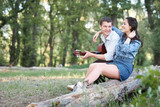 young couple sitting on a log in the forest and playing guitar, summer nature, romantic feelings - 220852861