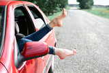 young woman driver resting in a red car, put her feet on the car window, happy travel concept - 220852897