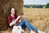 the girl with the phone sitting near a haystack - 220853003