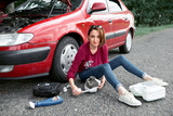 a young girl sits near a broken car and makes repairs to the electric generator, next to her there are bad parts, tools and first aid kit - 220853226