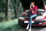 a young girl stands at a broken car and looks at the engine, does not understand how to repair - 220853255