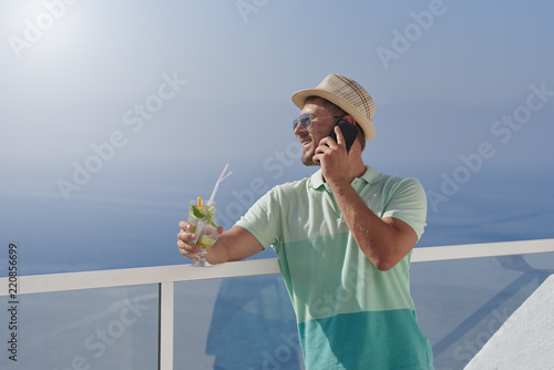 Happy man in sun hat talking on mobile phone and looking at sea from balcony . fea29bfaf811