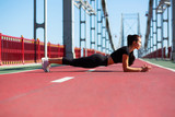 Athletic young model doing plank exercise outdoor at the bridge in sunny morning - 220857497