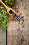 Juniper branch and wooden spoon with berries on a wooden background. - 220862446