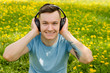 Portrait of a young guy listening to music on headphones and sitting on green grass with dandelions.