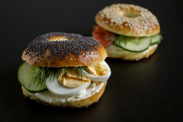 bagels with egg and cucumber on black background.