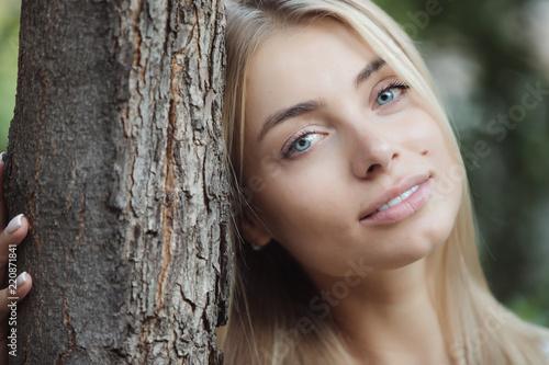 Kobieta opiera głowę drzewny bagażnik, niebieskie oko ładna dziewczyna
