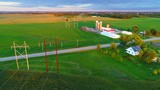 Scenic aerial view of power lines crossing fertile American heartland at dusk.  - 220874497