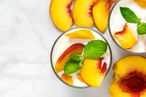 two glasses of healthy fruit yogurt with fresh peaches and mint on white marble table. healthy breakfast. top view