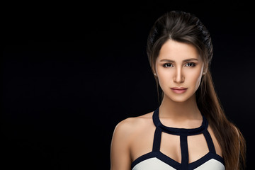 Front view of brunette woman in stylish dress confident and seductive looking at camera, posing at studio at black background. Brunette girl with perfect makeup and hairstyle. Concept of beauty salon. © Вячеслав Косько