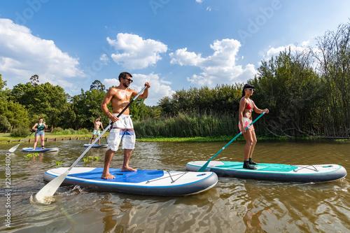 Leinwanddruck Bild Men and women stand up paddleboarding
