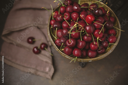 Foto Murales Freshly Picked Cherries in an Antique Scale on Warm Brown Background