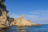 Seascape with a rocky shore in a clear sunny day. Large rocks in the sea near the coastline. Nature of Costa Brava, Spain. Wild rocks in the sea against a blue clear sky.