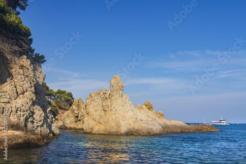 Leinwandbild Motiv Seascape with a rocky shore in a clear sunny day. Large rocks in the sea near the coastline. Nature of Costa Brava, Spain. Wild rocks in the sea against a blue clear sky.